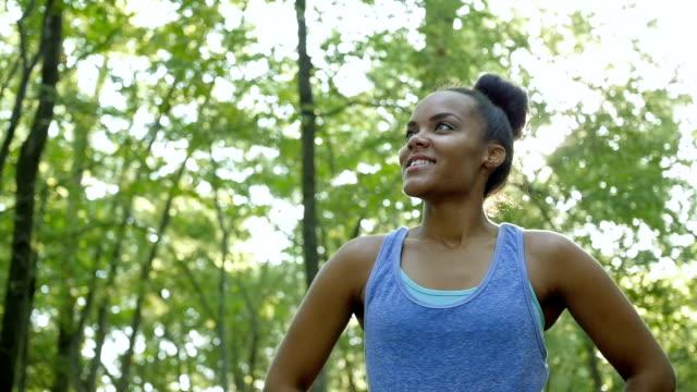 vídeos de stock, filmes e b-roll de afro-americana mulher atlética calçado para treino para descansar e verificar vibração - coque cabelo para cima