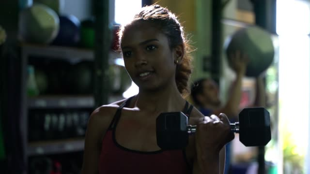 african american beautiful woman lifting weights at the gym - body building stock videos & royalty-free footage
