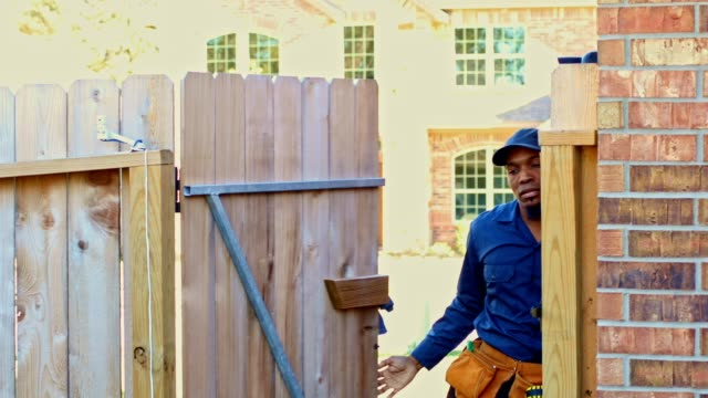 African American Blue Collar Worker coming through backyard gate with tools ready to work