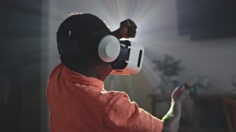 vídeos y material grabado en eventos de stock de slo mo. african american boy steers with hands as he plays virtual reality racing game. - simulador de realidad virtual