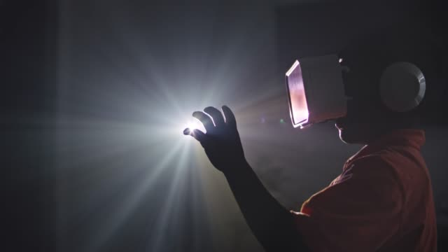 slo mo. african american boy wearing virtual reality headset holds hand up into the light of a projector. - luminosità video stock e b–roll