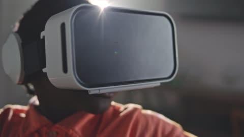 vídeos y material grabado en eventos de stock de cu slo mo. african american boy wearing vr headset turns quickly and motions with hands. - simulador de realidad virtual