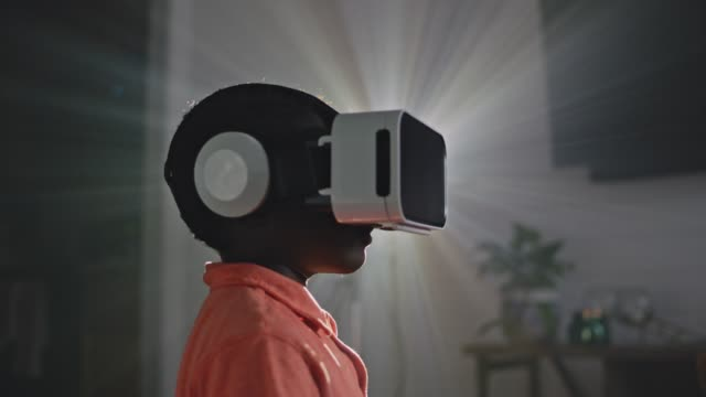 SLO MO. African American boy with VR headset stands in profile against the light of a projector.