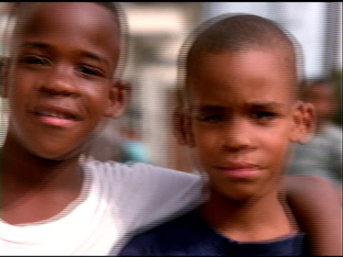african american boys, one with arm around others shoulders, look to camera - menschlicher arm stock-videos und b-roll-filmmaterial