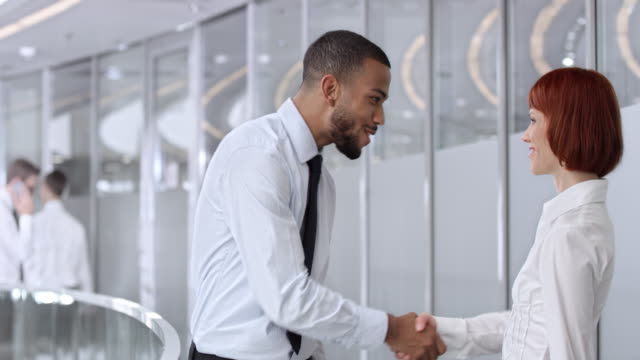 DS African American business man greeting his colleague in corporate hallway