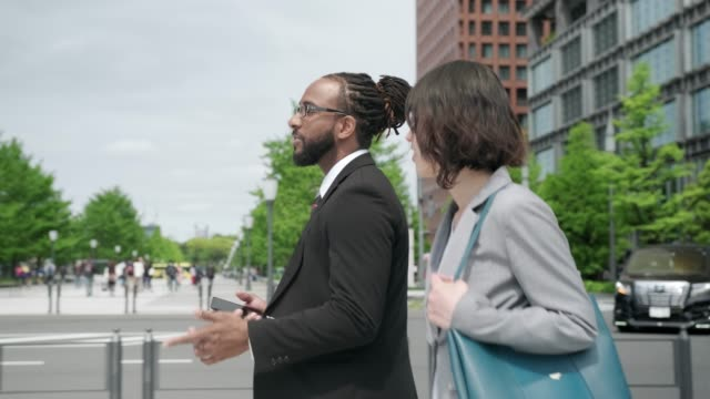 african american businessman and japanese businesswoman walking on the street and looking at smart phone - bonding stock videos & royalty-free footage