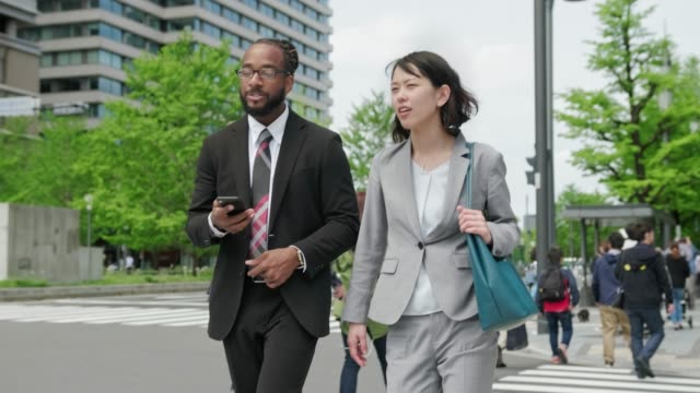 african american businessman and japanese businesswoman walking on the street and using smart phone - bonding stock videos & royalty-free footage