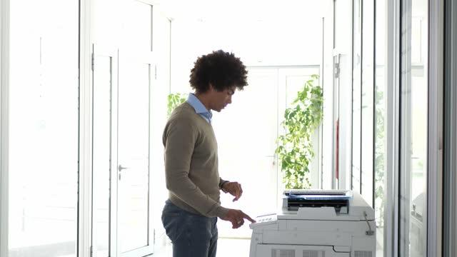 stockvideo's en b-roll-footage met afrikaanse amerikaanse zakenman in bureau dat kopieerapparaat, na lockdown met behulp van - drukker