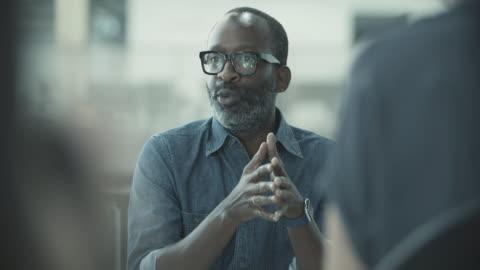 vídeos y material grabado en eventos de stock de african american businessman leading a meeting - liderazgo