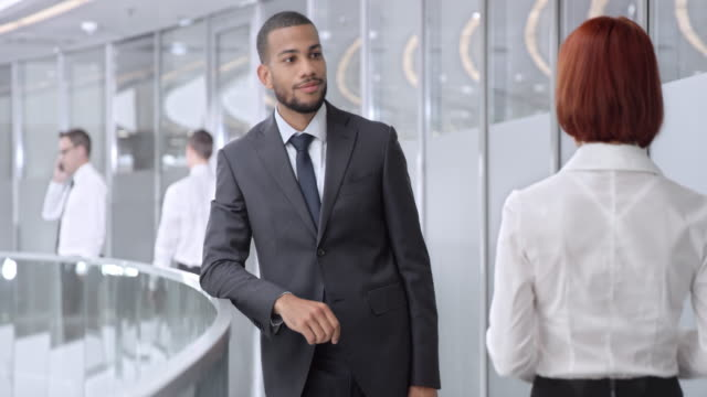 DS African American businessman meeting with woman in corporate hallway