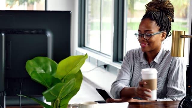 アフリカ系アメリカ人のビジネスウーマンは、休憩中にソーシャルメディアを閲覧します - 鉢植え点の映像素材/bロール