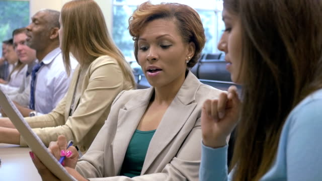 stockvideo's en b-roll-footage met african american businesswoman taking notes during seminar or business conference - banenbeurs