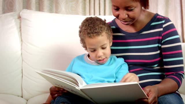 stockvideo's en b-roll-footage met hd: african american verzorger lezing met kleine jongen - prentenboek