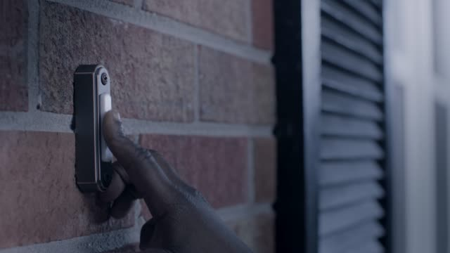 CU. African American child's hand rings doorbell outside brick house at night.