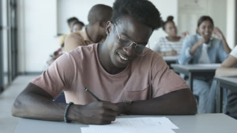 african american college student with glasses writes at desk, close up - educational exam stock videos & royalty-free footage