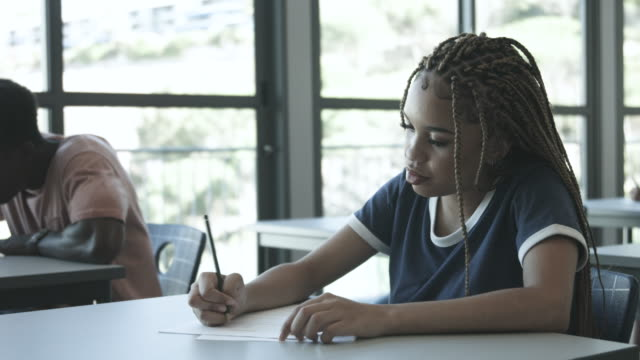 african american college student writes at desk, close up - braided hair stock videos & royalty-free footage