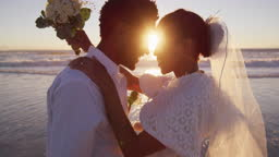 African american couple in love getting married, looking at each other on the beach at sunset