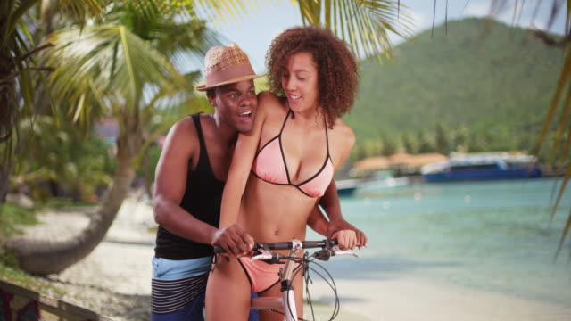 african american couple ride their beach cruiser along the shore in the caribbean - board shorts stock videos and b-roll footage