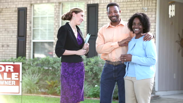African American couple with realtor buying house