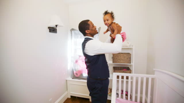 african american dad at home with his baby daughter in her nursery room. - genderblend stock videos & royalty-free footage