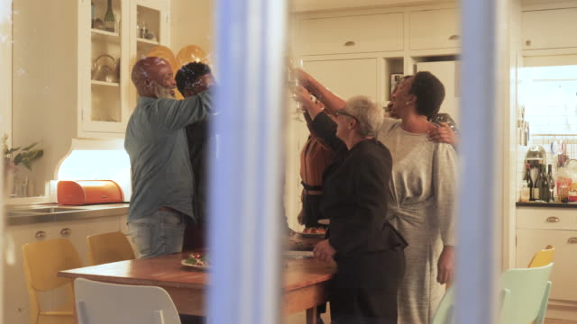 african american family cheers at dining table, medium shot - 20 24 år bildbanksvideor och videomaterial från bakom kulisserna