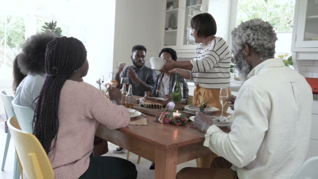 african american family has christmas dinner, medium shot - meal stock videos & royalty-free footage