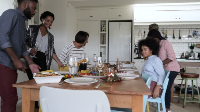 African American family in kitchen on Christmas, tracking shot