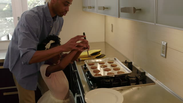 african american family makes cookies together int he kitchen - stereotypically middle class stock videos & royalty-free footage