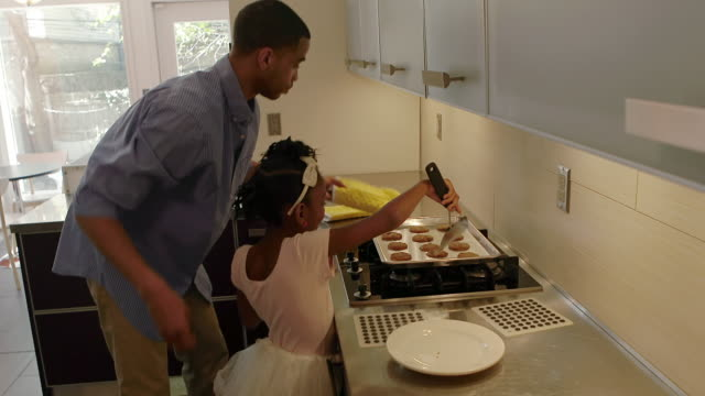 African American Family Makes cookies together int he kitchen