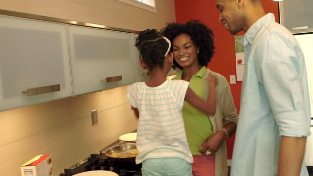African American Family Makes Pancakes together in the kitchen