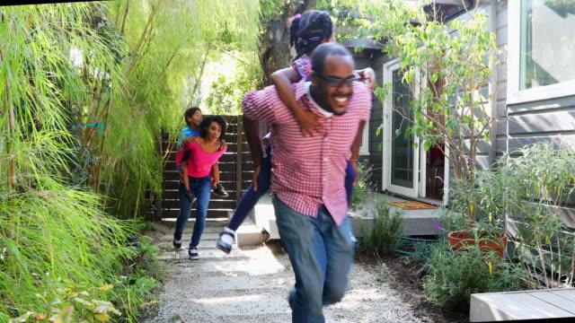 Afroamerikanische Familie Piggy Rückhalt durch den Garten