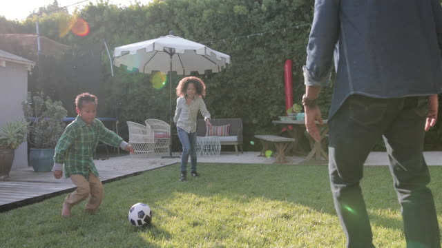 african american family playing football in yard - domestic garden stock videos & royalty-free footage