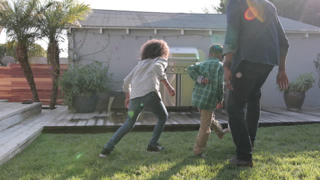 african american family playing football in yard - african american ethnicity stock videos & royalty-free footage