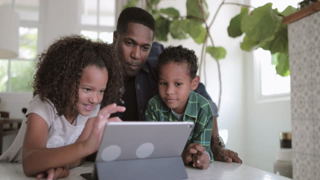 african american family playing with digital tablet - maschi video stock e b–roll