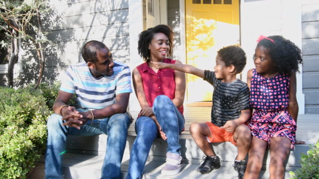 African American family sitting on doorstep talking and smiling