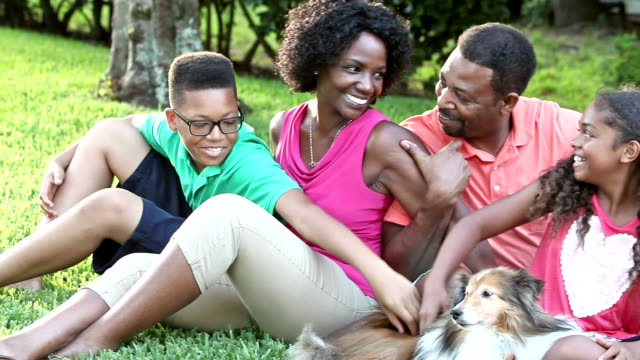 African American family sitting on grass with pet dog