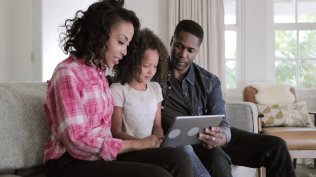african american family watching video on digital tablet at home - african american culture stock videos & royalty-free footage