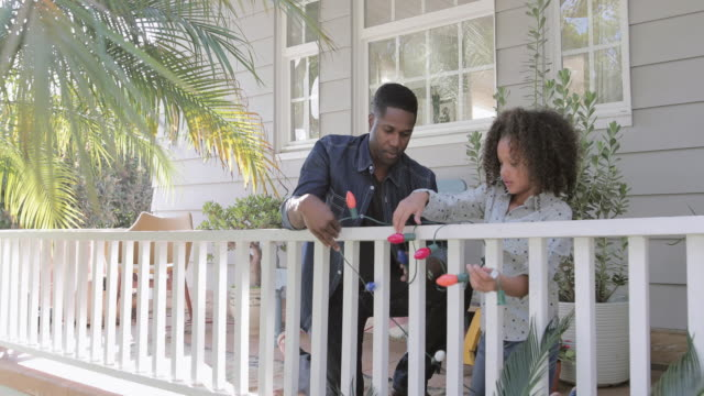 african american father and daughter hanging christmas lights outdoors - hanging stock videos & royalty-free footage