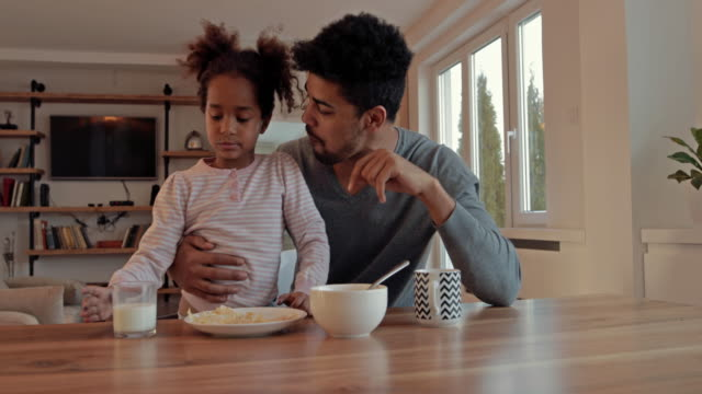 African American father and daughter having fun during breakfast time at home.