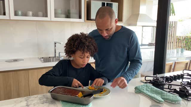 african american father and his son eating cake in the kitchen at home. - genderblend stock videos & royalty-free footage