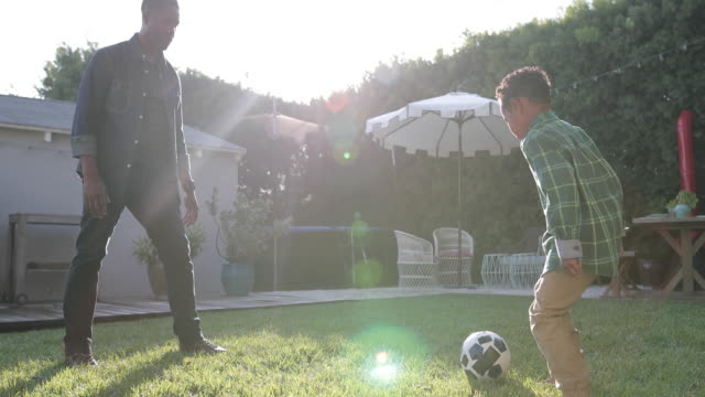 African American father and son playing football in yard