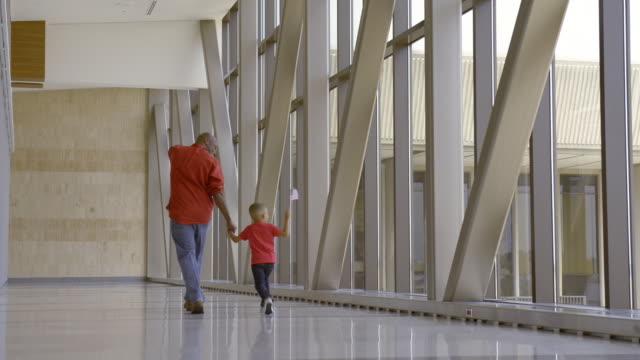 vídeos de stock, filmes e b-roll de african american father and son walking in airport - vista traseira