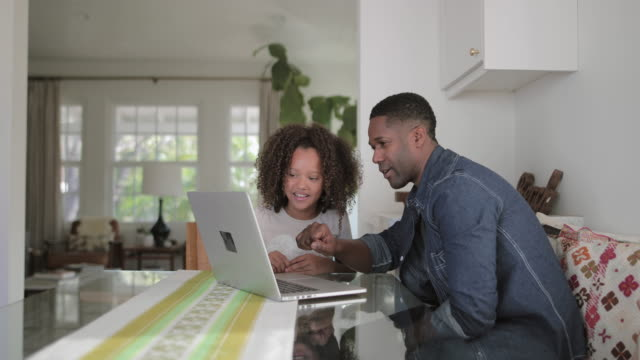 African American father helping daughter with homework using laptop
