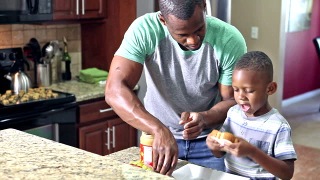 african american father making sandwich for son - making a sandwich stock videos and b-roll footage