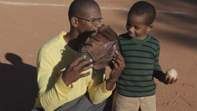 african american father playing baseball with son - baseball diamond stock videos and b-roll footage
