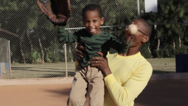 african american father playing baseball with son - 男の子点の映像素材/bロール
