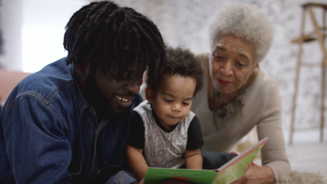 African American Father Reading With His Mom and Toddler Son