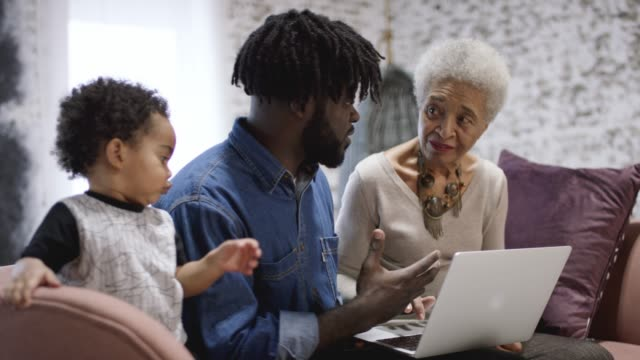 african american father teaching his mother how to use the computer - young family stock videos & royalty-free footage