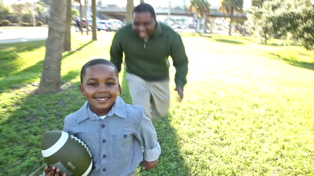 African American father with little boy and football