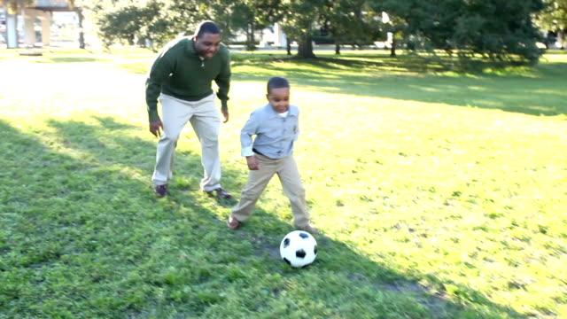 vidéos et rushes de père afro-américain avec petit garçon jouant au soccer - petits garçons